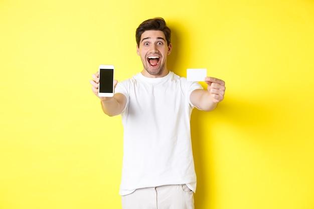 Bel homme caucasien montrant l'écran du smartphone et la carte de crédit, concept de banque mobile et achats en ligne, fond jaune.