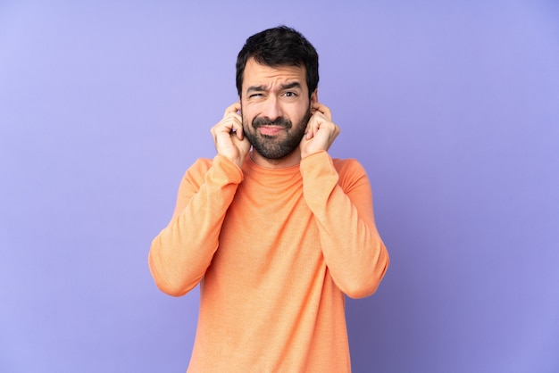 Bel homme caucasien sur mur violet isolé frustré et couvrant les oreilles