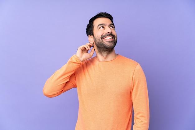 Bel homme caucasien sur mur violet en pensant à une idée