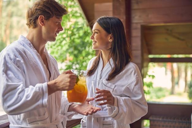 Bel homme et charmante belle femme se regardant le verre de limonade orange
