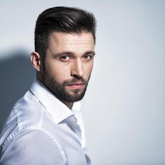 Bel homme en chemise blanche, posant. mec attrayant avec une coiffure de mode. homme confiant avec une barbe courte. garçon adulte aux cheveux bruns. portrait en gros plan.