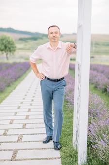 Bel homme en chemise légère profitant de la promenade, debout sur le fond du champ de lavande, s'appuyant sur une arche en bois blanc