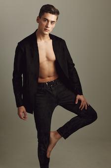 Bel homme en chemise noire se dresse avec une jambe pliée posant des modèles attrayants.