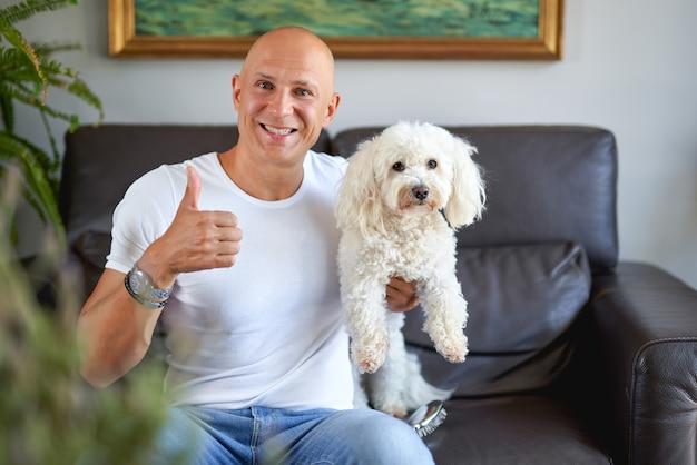 Bel homme avec un chien blanc à la maison sur un canapé