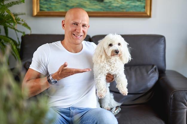 Bel homme avec un chien blanc mignon à la maison sur un canapé