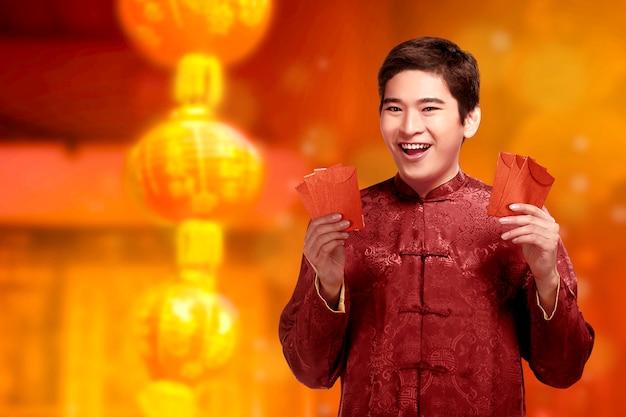 Bel homme chinois avec des vêtements cheongsam montrant des enveloppes rouges sur ses mains