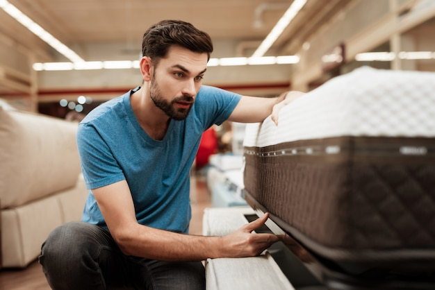 Bel homme choisir matelas dans magasin de meubles