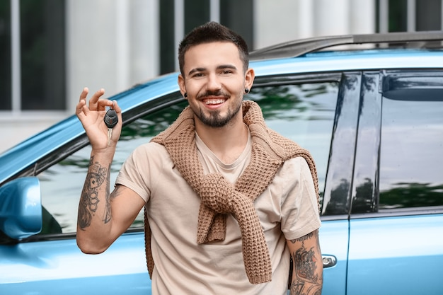 Bel homme avec clé de voiture près d'une voiture moderne