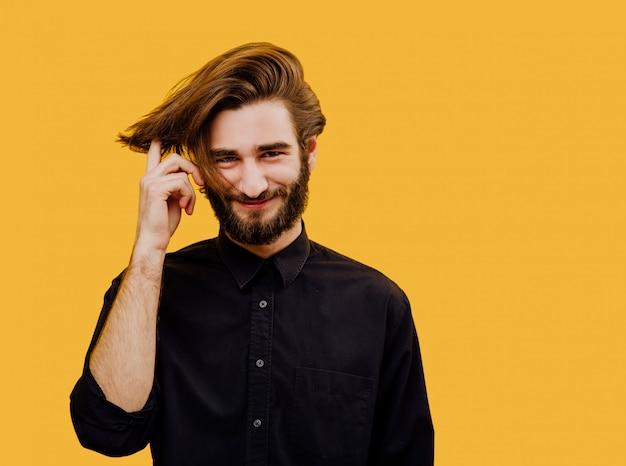 Bel homme avec une coiffure moderne, souriant émotionnellement dans le cadre, isolé sur fond jaune,