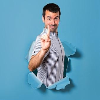 Bel homme en comptant un à travers un trou de papier