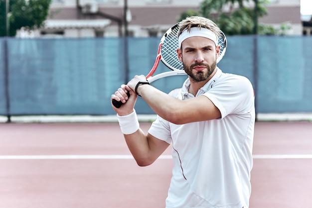 Le bel homme de concentration joue au tennis