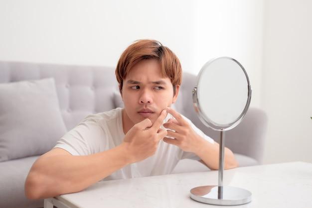 Bel homme concentré examinant de manière critique la peau de son visage dans le miroir et touchant ses joues avec les doigts