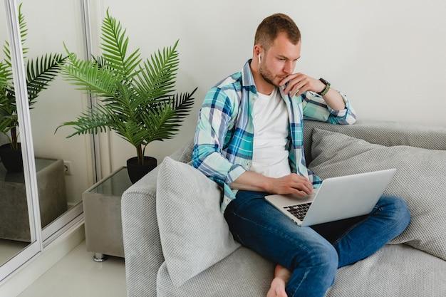Bel homme concentré occupé en chemise assis détendu sur un canapé à la maison à table travaillant en ligne sur un ordinateur portable depuis la maison