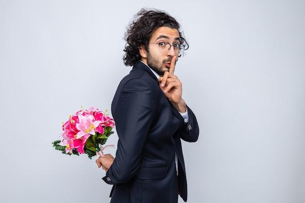 Bel homme en costume avec bouquet de fleurs derrière le dos regardant la caméra faisant un geste de silence avec le doigt sur les lèvres célébrant la journée internationale de la femme le 8 mars debout sur fond blanc