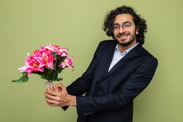 Bel homme en costume avec bouquet de fleurs à sourire joyeusement célébrer