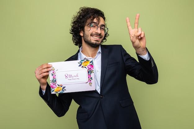 Bel homme en costume tenant une carte de voeux à sourire gaiement montrant v-sign, célébrant la journée internationale de la femme le 8 mars