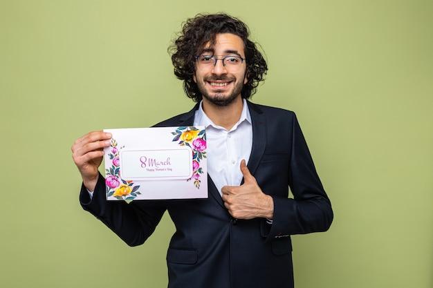 Bel homme en costume tenant une carte de voeux à sourire joyeusement montrant les pouces vers le haut célébrant la journée internationale de la femme le 8 mars
