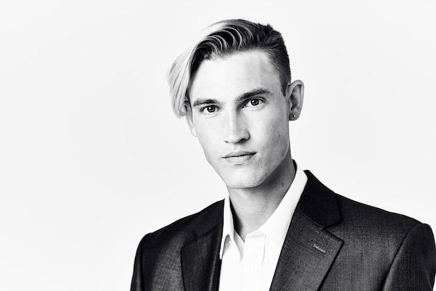 Bel homme en costume tient sa main près de son visage coiffure à la mode photo noir et blanc
