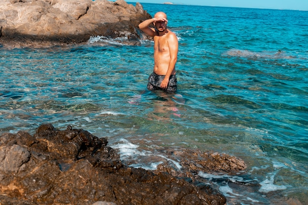 Bel homme sur la côte rocheuse marine