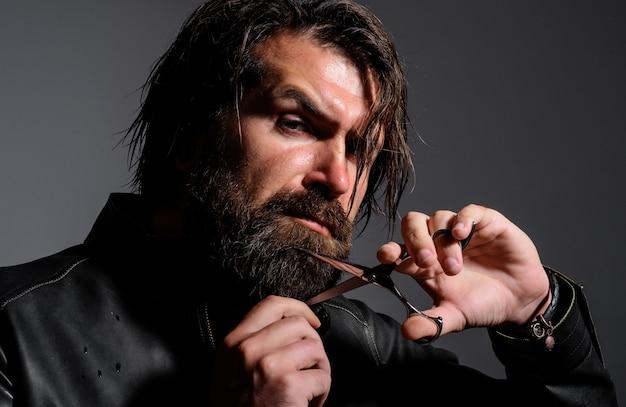 Bel homme coupant la barbe avec des ciseaux. publicité de salon de coiffure. salon pour hommes.