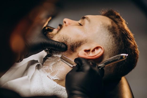 Bel homme coupe la barbe dans un salon de coiffure