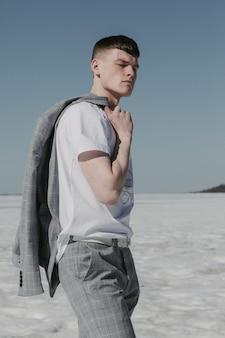 Bel homme avec une coupe de cheveux française debout au soleil tenant la veste sur son épaule.