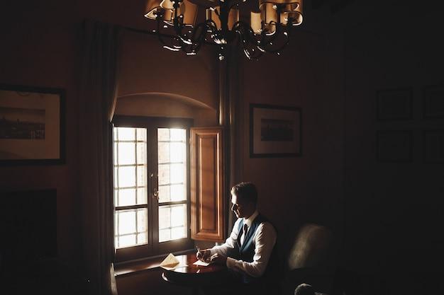 Bel homme avec une cravate rose est assis à la table et écrit une lettre dans la chambre noire