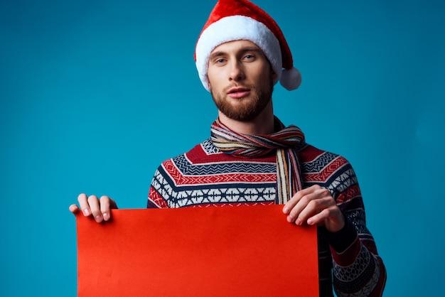 Bel homme dans un bonnet de noel tenant une bannière vacances fond isolé