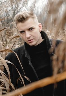 Bel homme dans un champ avec de hautes herbes en automne, portrait d'art de l'homme