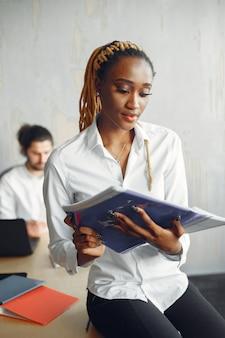 Bel homme dans une chemise blanche. femme africaine avec partenaire. guy avec un ordinateur portable.