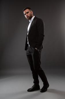 Un bel homme dans un costume noir et une chemise blanche.