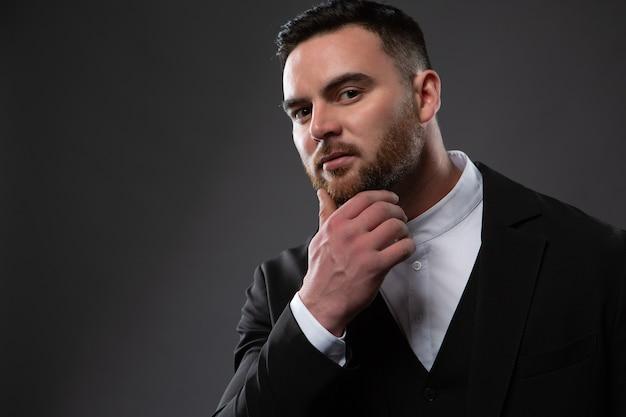 Un Bel Homme Dans Un Costume Noir Et Une Chemise Blanche. Photo Premium