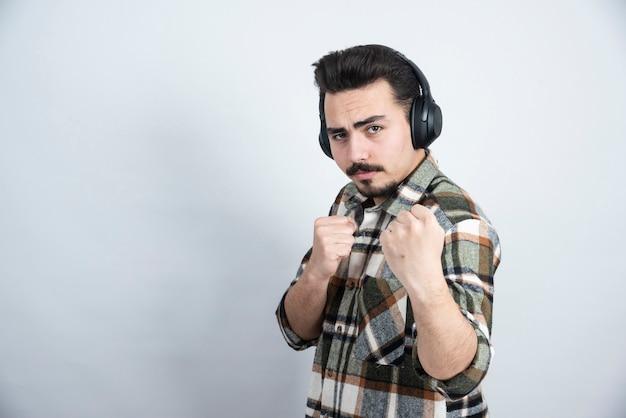 Bel homme dans les écouteurs debout et posant à la caméra.