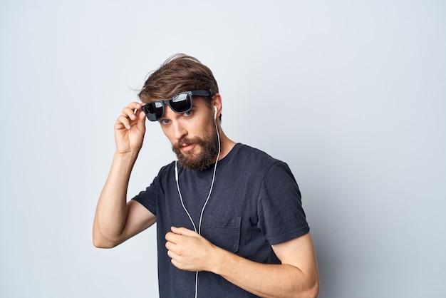 Bel homme dans une musique de tshirt noir dans un fond clair de mouvement d'écouteurs