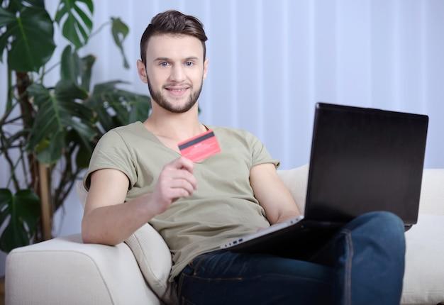 Bel homme dans le salon lumineux à l'aide de sa carte de crédit.