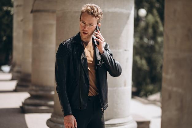 Bel homme dans des spectacles à l'aide de téléphone
