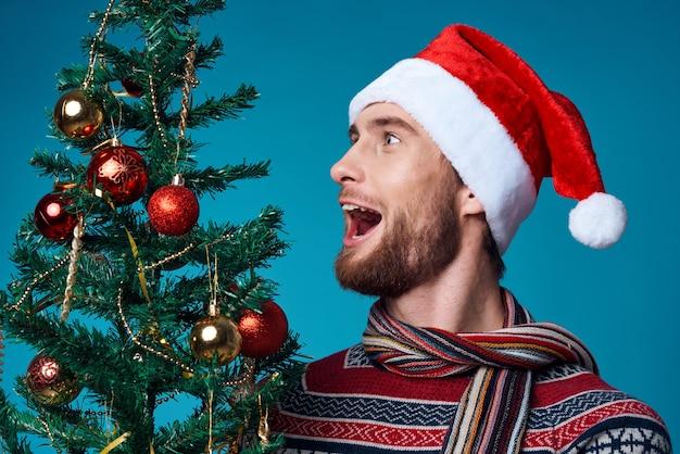Bel homme dans le studio de noël de décoration de vêtements de nouvel an posant