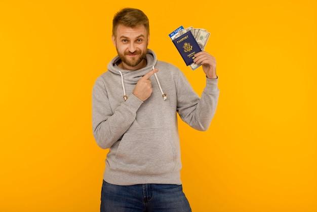 Un bel homme dans un sweat à capuche gris tient un passeport avec des billets d'avion et de l'argent