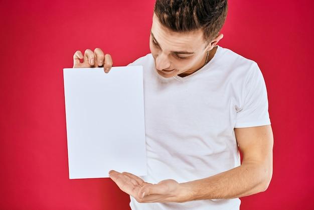 Bel homme dans un t-shirt tenant un papier vierge