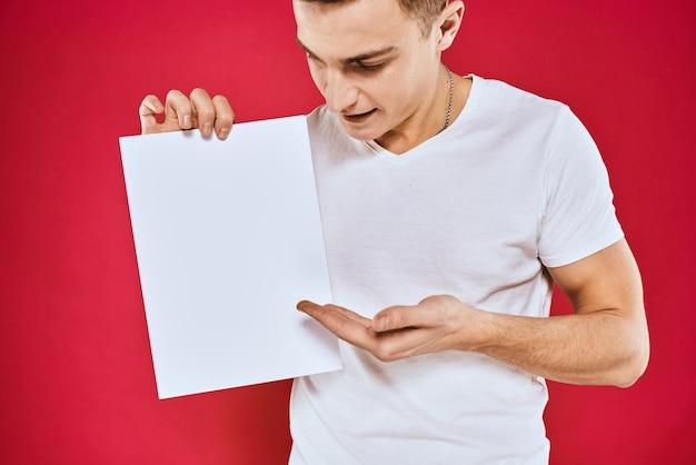 Bel homme dans un t-shirt tient une feuille blanche sans inscription