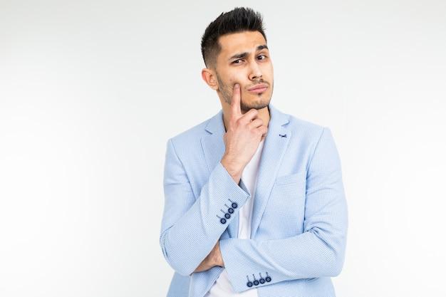 Bel homme dans une veste classique bleue offre une idée sur un fond blanc avec copie espace