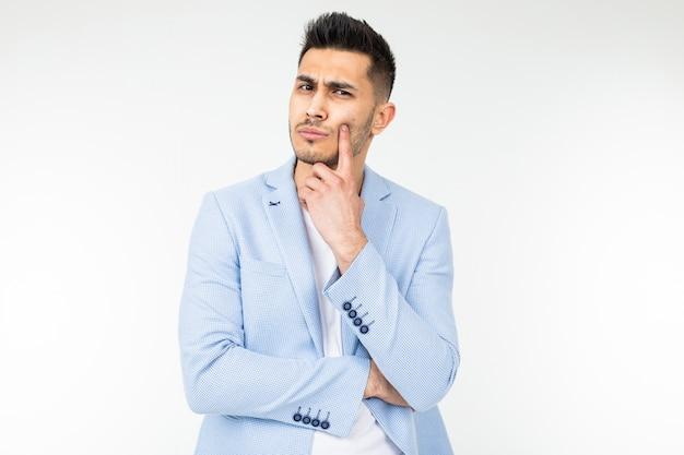 Bel homme dans une veste classique bleue propose une idée sur fond blanc avec espace copie.