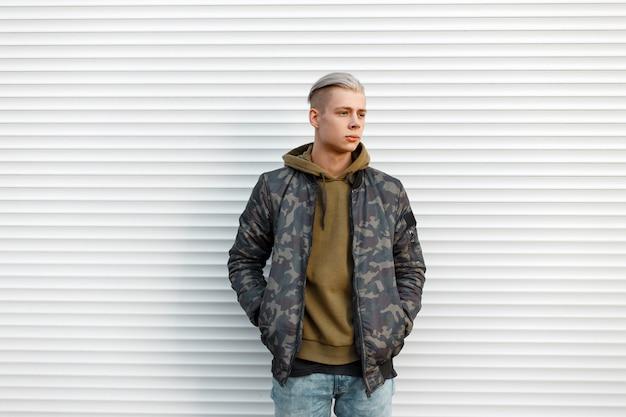Bel homme dans une veste militaire avec un sweat-shirt en jeans près de murs en métal blanc