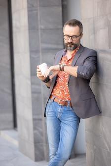 Bel homme dans des vêtements décontractés vérifiant le temps d'attente pour quelqu'un dans la ville
