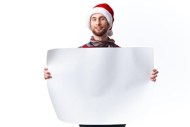 Bel homme dans des vêtements de nouvel an tenant un fond clair de bannière de vacances