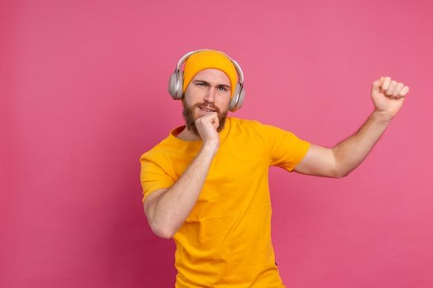 Bel homme en danse décontractée avec un casque isolé sur fond rose