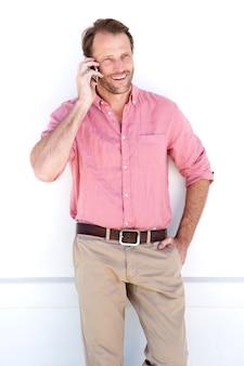Bel homme debout par un mur blanc avec un téléphone portable