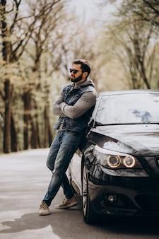 Bel homme debout près de la voiture dans le parc