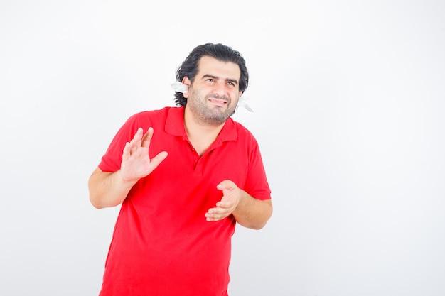 Bel homme debout avec des serviettes dans les oreilles, étirant les mains comme tenant quelque chose en t-shirt rouge et à la vue de face, heureux.