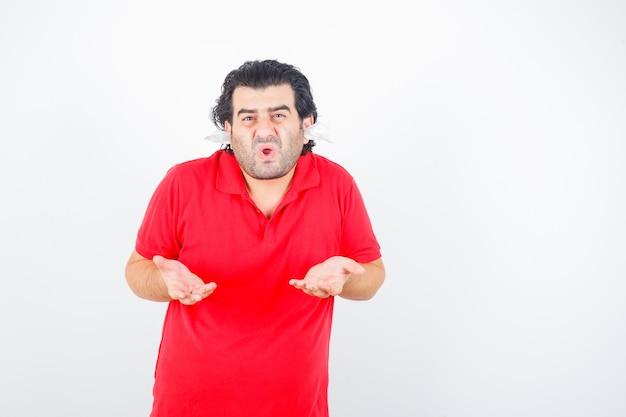 Bel homme debout avec des serviettes dans les oreilles, étirant les mains de manière interrogative en t-shirt rouge et à la perplexité, vue de face.